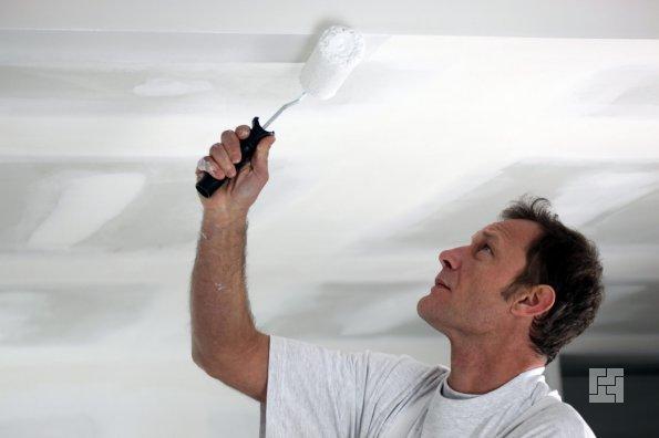 мужчина красит потолок с помощью валика
