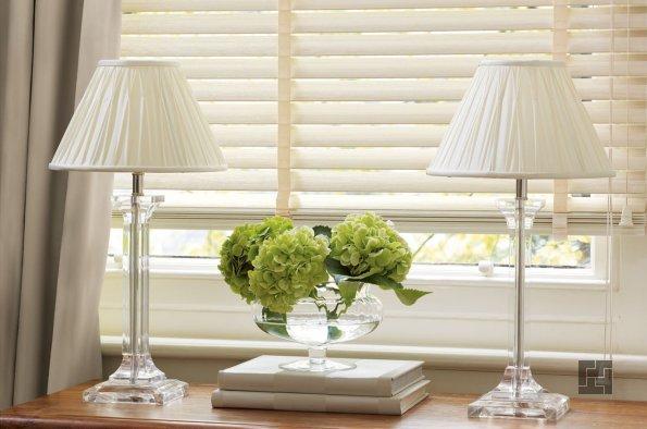 изящные настольные лампы на окне с жалюзи