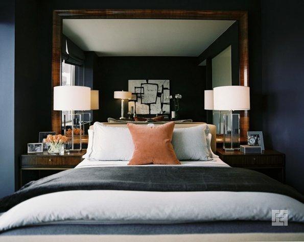 Большое зеркало в раме у изголовья кровати в спальне