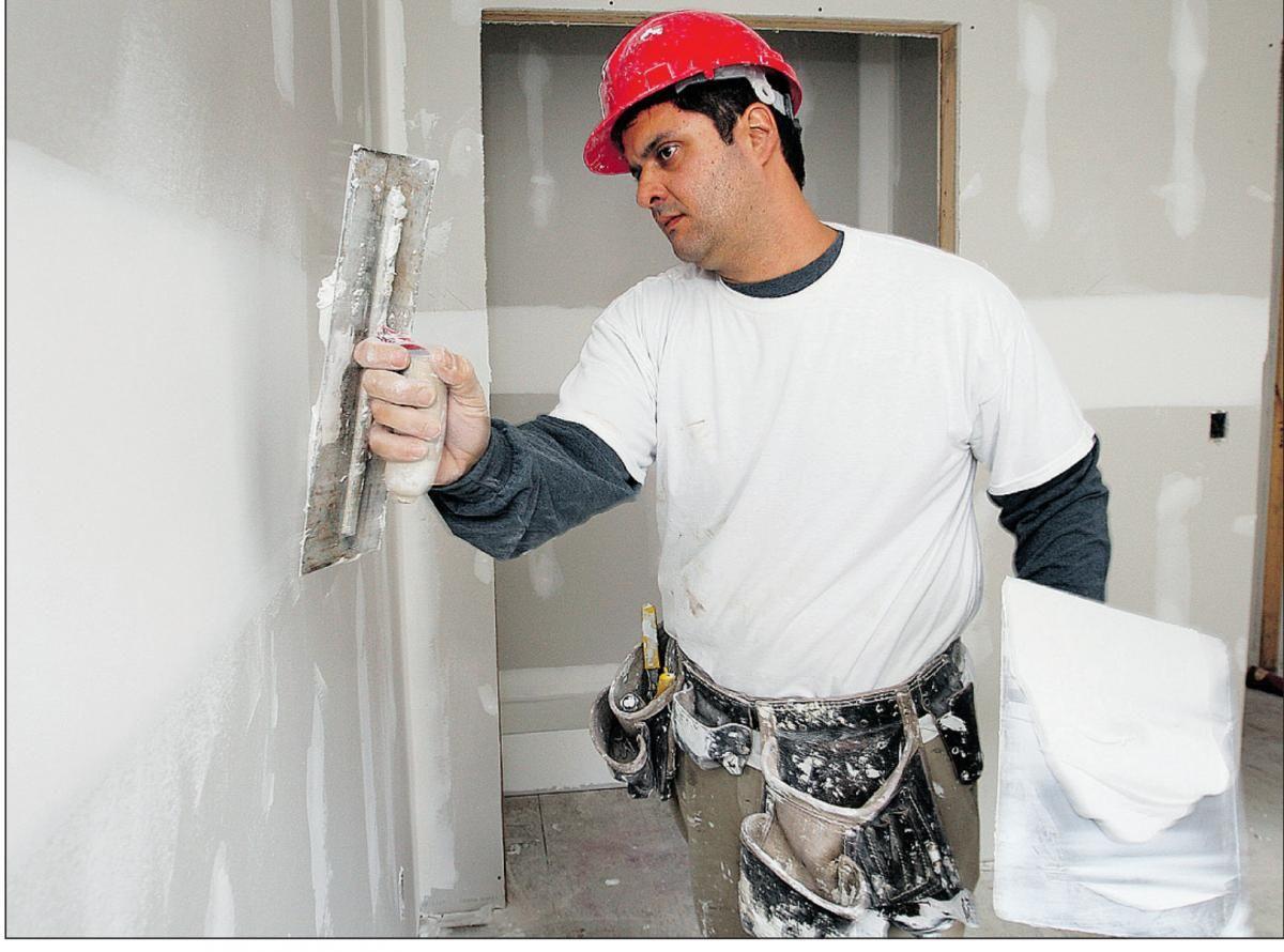 Мужчина шпаклюет стену