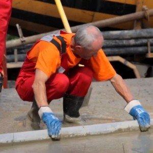 Выравнивание поверхности залитого фундамента деревянной доской