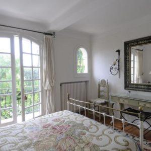 Светлая французская спальня с кованой кроватью