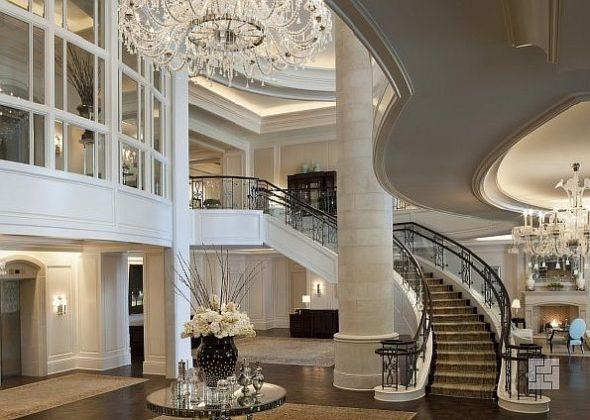 Интерьер холла в частном доме с дугообразной лестнице