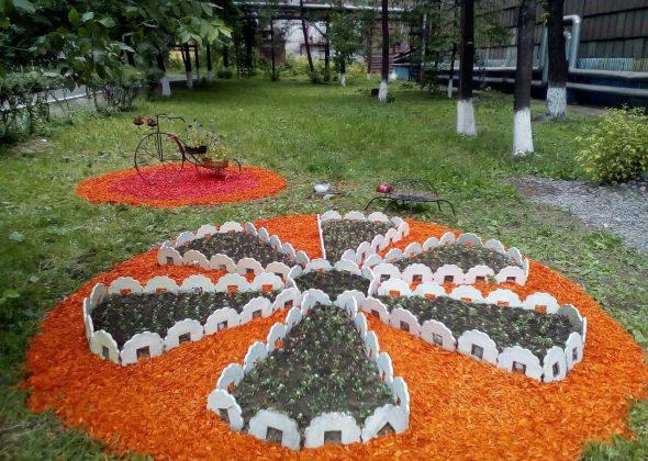 Клумба с декоративными щепками оранжевого цвета
