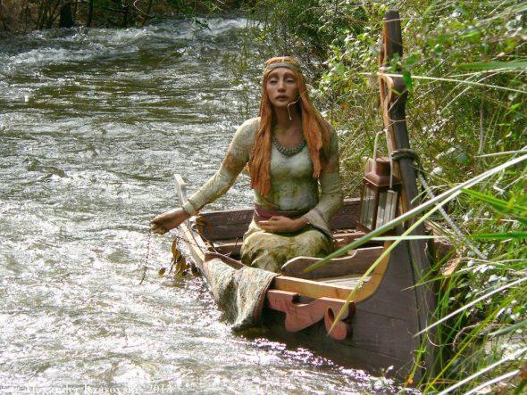 Скульптура девушки в лодке на берегу горной реки