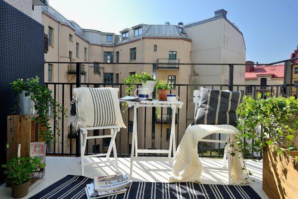 Открытый балкон с складной мебелю и цветами