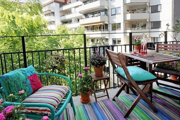 Балкон в ярких цветах и складной мебелью