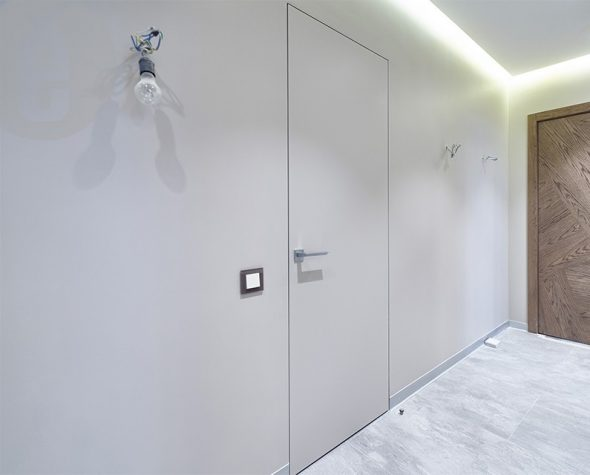 Дверь без наличников на белой стене