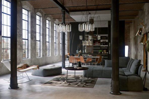 Просторная гостиная с большими окнами в индустриальном стиле