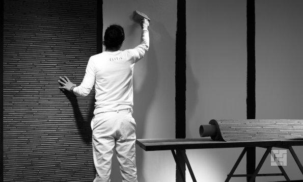 мужчина красит стену малярной кистью