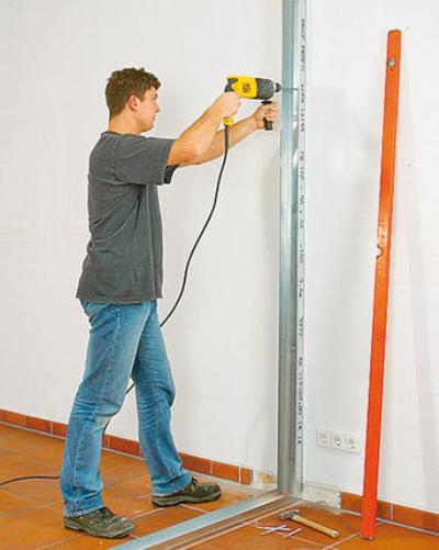 Монтаж вертикальных направляющих к несущим стенам