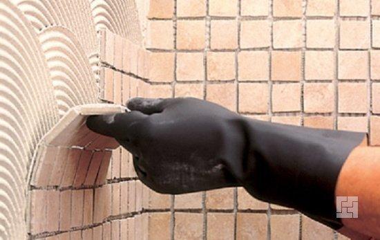 Раствор для укладки наносится на стены, излишки удаляются, затем крепится мозаика