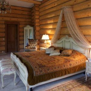 Спальня в доме из оцилиндрованного бревна