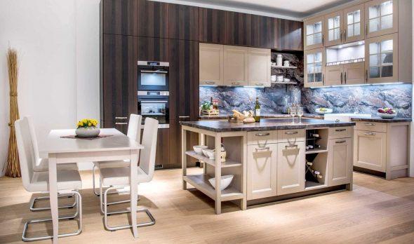 Просторная кухня со светлым гарнитуром и обеденной зоной
