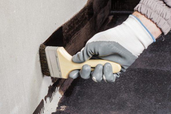 Применение мастики в месте примыкания стены