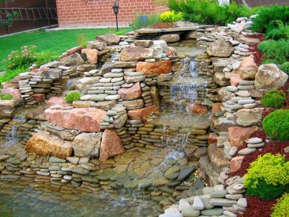 оригинальное оформление сада с помощью каменного водопада