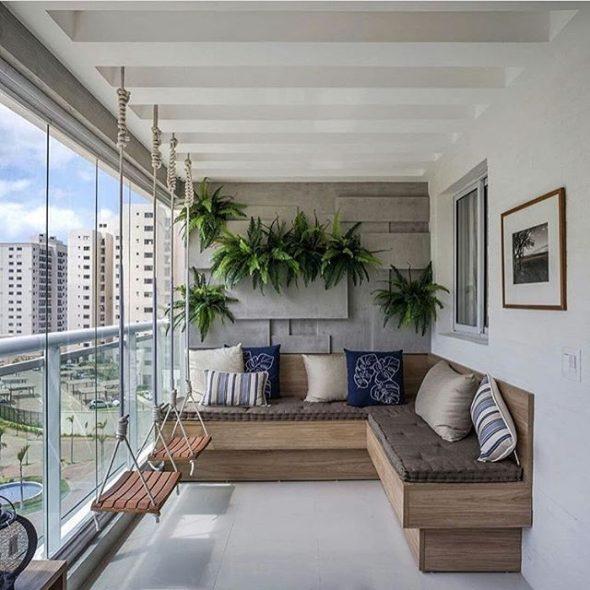 Просторный балкон с угловым диваном и качелями