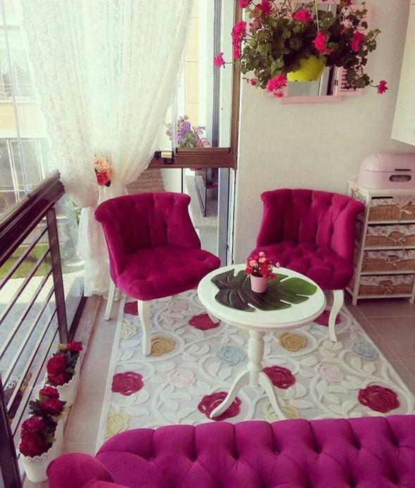 Балкон с мягкой мебелью розового цвета и столиком