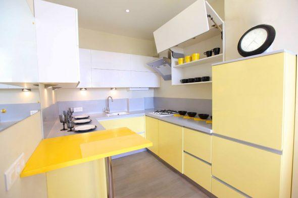Интерьер светло-жёлтой кухни с белыми шкафчиками