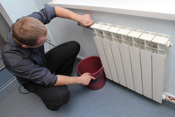мужчина открывает кран радиатора