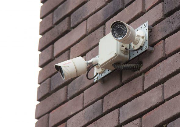 Камера видеонаблюдения с проводами, идущими в здание